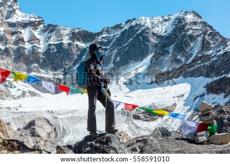 Female Mountain Climber staying on rocky Ridge in high Altitude Mountains along with traditional colorful Nepalese Flags and snowy Summits and Glacier on Background