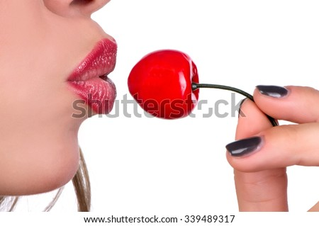 Female mouth with red lipstick lips and fingers with berry cherr