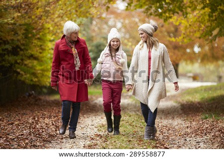 Female Multl Generation Family Walking Along Autumn Path