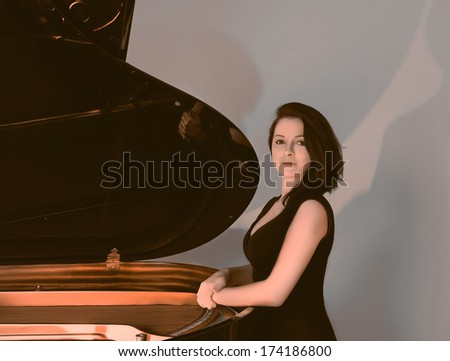 Female musician standing by the grand piano, toned image - stock photo