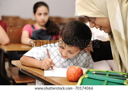 Female Muslim teacher helping a little pupil in the classroom - stock photo
