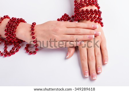 Female nail salon. French manicure with red beads. - stock photo