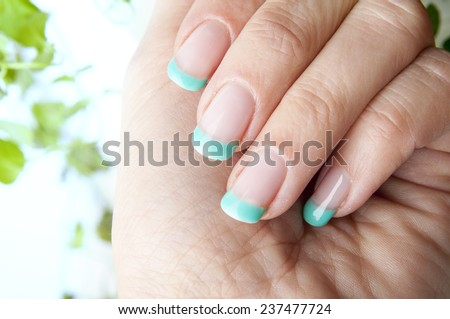 Female nails with beautiful manicure design and fresh mint leaves - stock photo
