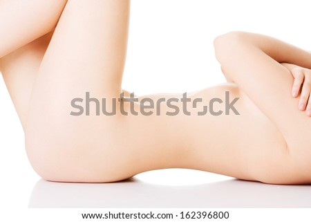 Female naked body lying on the floor. Closeup. Isolated on white.