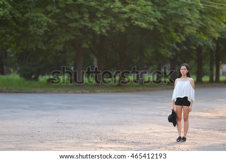 female nature keeps his hat summer sun sunset looks pleased. azitka woman black hair white shirt black shorts out trees around.