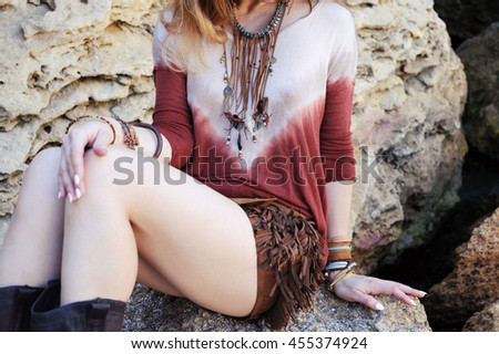 Female neck, chest and hands with boho chic bracelets and leather necklace, outdoor fashion photo with sitting girl on a rock stones - stock photo