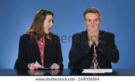 Female newscaster looking at male co-worker as if he has said something terrible.
