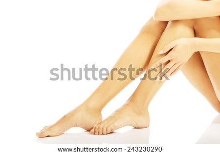 Female nude legs touching by a hand - stock photo
