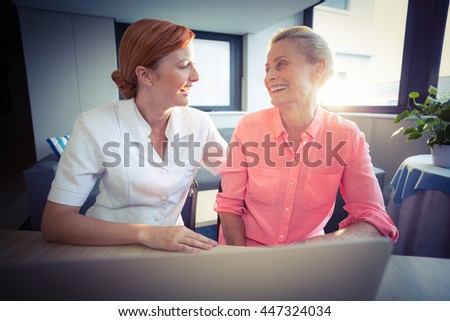 Female nurse and senior woman smiling while using laptop at home