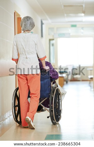 female nurse carer and aged elderly patient woman in wheelchair at clinic hallway