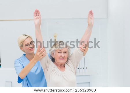 Female nurse helping female patient in exercising at clinic - stock photo