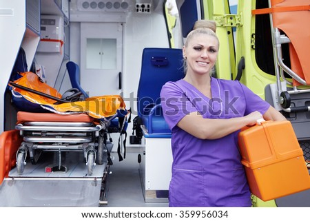 Female-nurse in hands medical equipments standing about ambulance  - stock photo