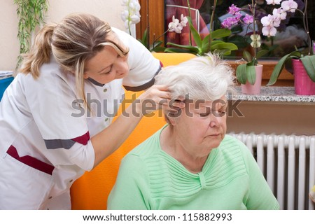 female Nurse massages the head of a senior