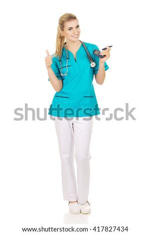 Female nurse or doctor holding glucometer - stock photo