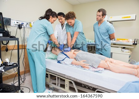 Female nurse performing CRP on dummy patient while doctor and colleagues looking at it in hospital room - stock photo