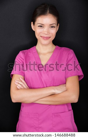 Female nurse portrait happy confident in pink scrubs on black background. Young woman medical professional nurse or doctor standing cross-armed looking at camera smiling. Multiracial Asian model. - stock photo