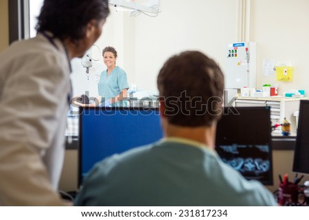 Female nurse preparing patient for CT scan with colleague and doctor in hospital lab - stock photo