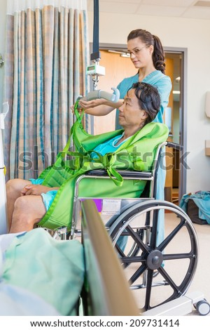 Female nurse removing straps from hydraulic lift with patient on wheelchair in hospital - stock photo