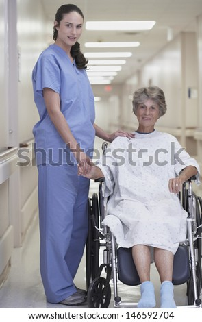 Female nurse standing with senior female patient sitting in wheelchair