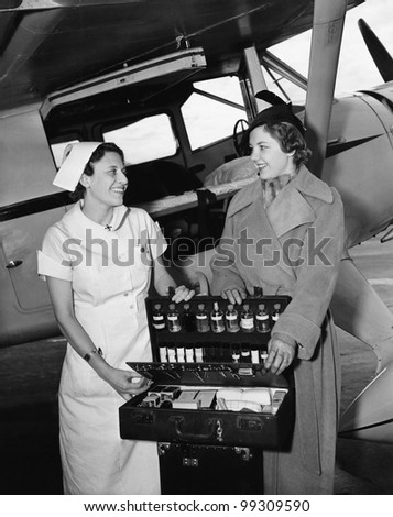 Female nurse with a young woman standing in front of an airplane and opening a medicine box - stock photo