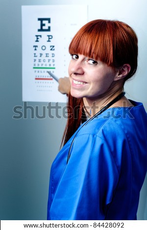 female oculist doctor examining patient with an eye chart behind - stock photo
