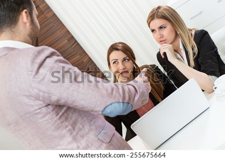 Female office employees caught by manager at inappropriate social networking during working hours, but they don't care and they are smiling,  - stock photo