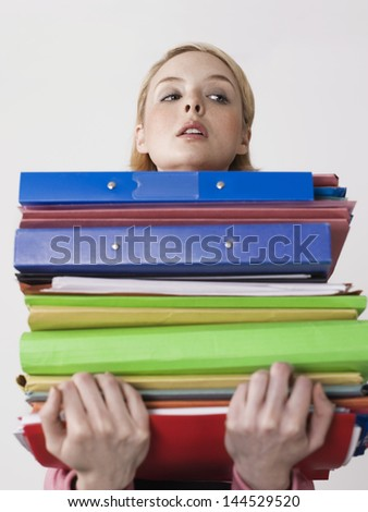 Female office worker carrying heavy binders against gray background - stock photo