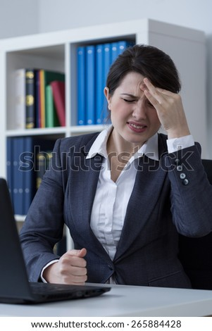 Female office worker having migraine at work - stock photo