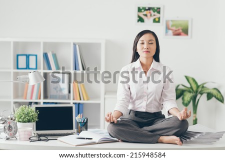 Female office worker meditating on her work place - stock photo