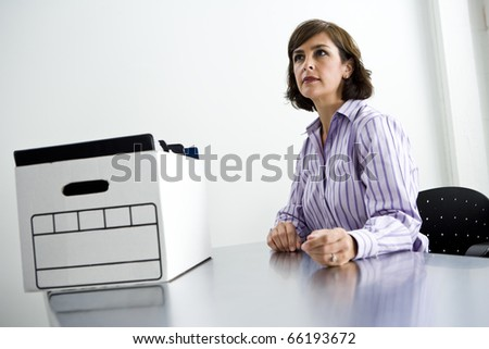 Female office worker, 40s, sitting at office table with cardboard file storage box