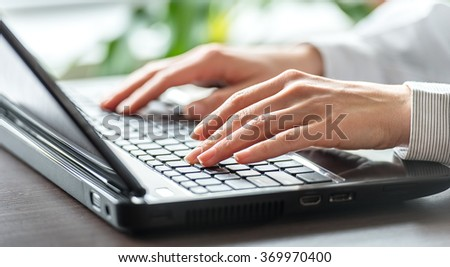 Female office worker typing on the keyboard. - stock photo