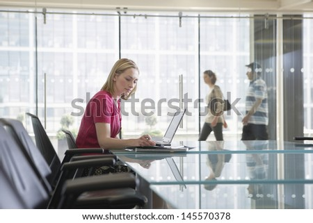 Female office worker using laptop in conference room as colleagues pass by