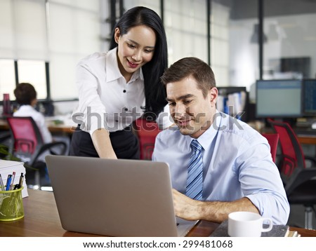 female office worker working together with caucasian expat colleague in office. - stock photo