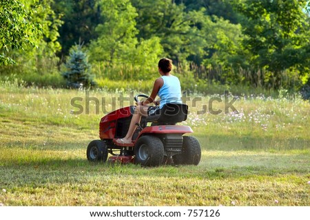 Female on a riding lawn mower cutting the grass - stock photo