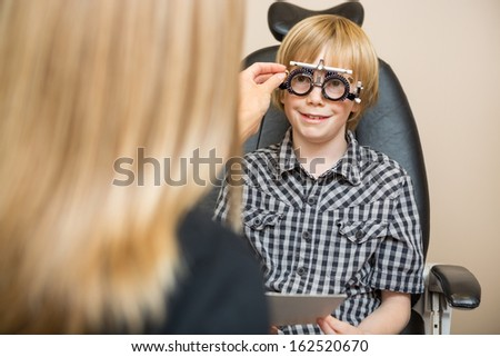 Female optician determining prescription values with optometric frame for boy in store - stock photo