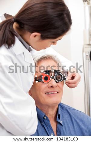 Female optometrist adjusting lens of trial frames on mature man - stock photo