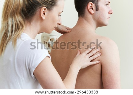 Female Osteopath Treating Male Patient With Shoulder Problem - stock photo