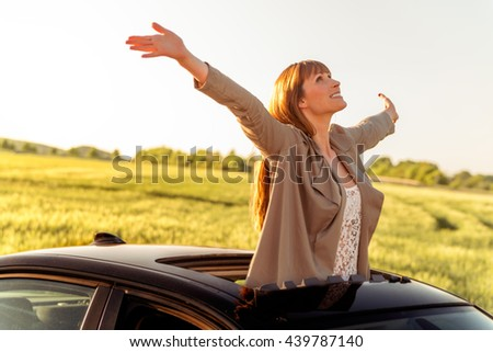 female outstretched from panorama roof - stock photo