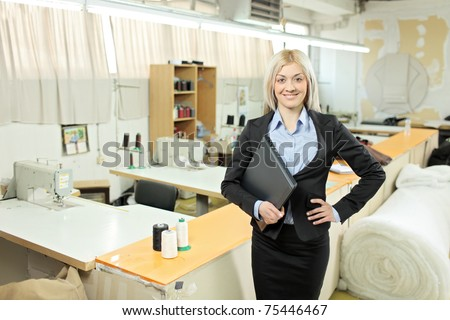 Female owner of a small business standing inside a textile factory holding a laptop computer in her hand - stock photo