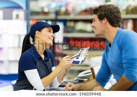 female paint store worker talking to customer over the counter - stock photo