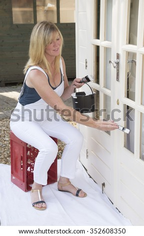 Female painter decorator using a paint brush