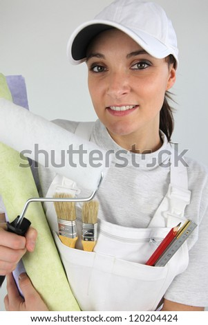 female painter with cap holding roller and wallpaper rolls - stock photo