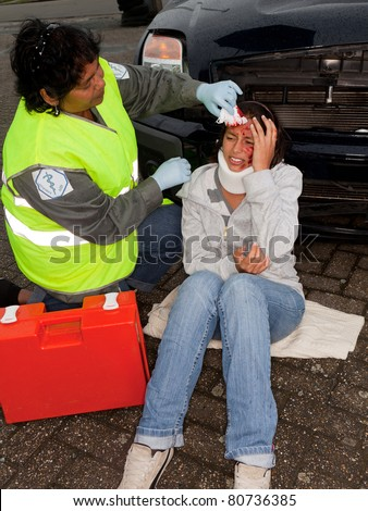 Female paramedic attending to a young car crash victim (the sleeve badges have been replaced by a non existing logo) - stock photo