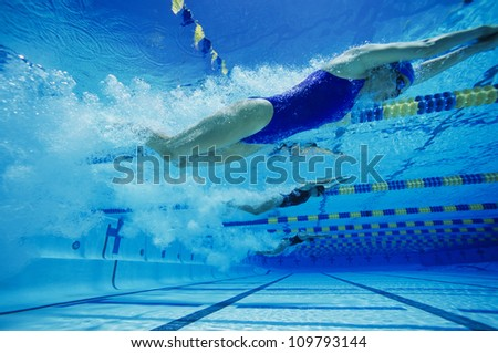 Female participants swimming underwater during a swimming race - stock photo