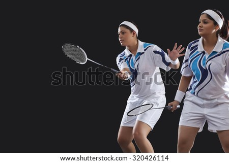 Female partners in sportswear playing badminton against black background