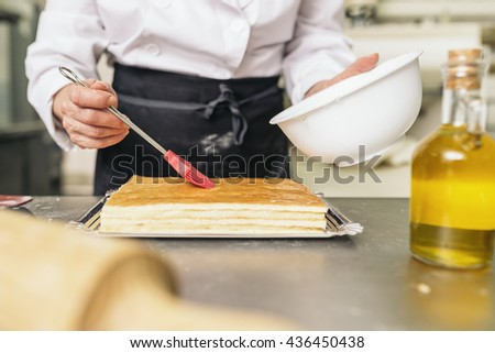 Female pastry chef decorating dessert in the kitchen. Cooking Concept.