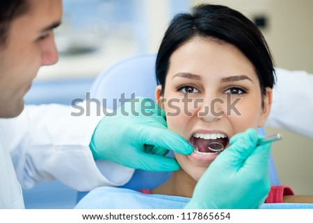 Female patient having her teeth examined by dental specialist - stock photo