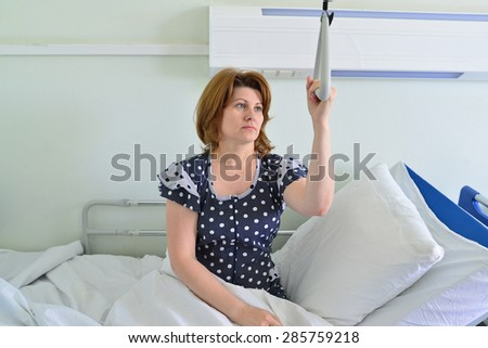 Female patient holding on to a device for lifting in hospital room - stock photo