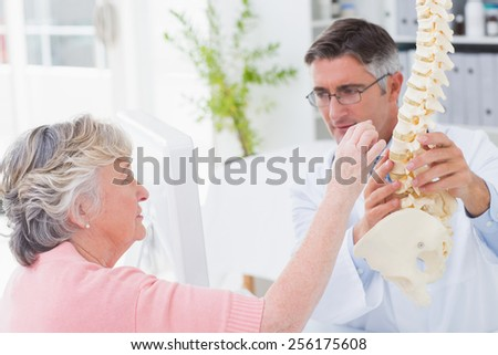 Female patient looking at anatomical spine while doctor explaining her in clinic - stock photo