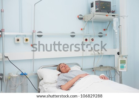 Female patient lying on a bed in hospital ward - stock photo